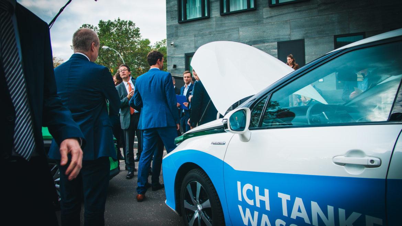 Bundesverkehrsminister Scheuer und Personen stehen vor einem Wasserstoff-Pkw