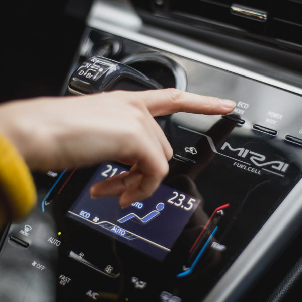 Hand pointing at button inside a fuell cell car