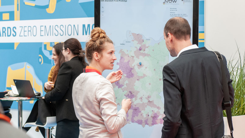 Personen stehen vor Touchscreen und schauen auf eine Deutschlandkarte mit Informationen zu Ladeinfrastruktur