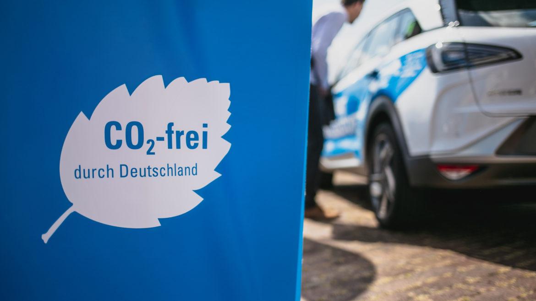 Fahne auf der steht CO2-frei durch Deutschland, im Hintergrund parkt ein Wasserstoff-Pkw